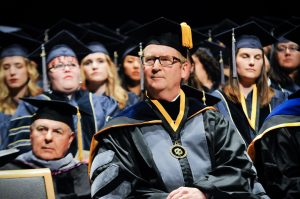 Dean Michael Lairmore listens to a speaker at this year's commencement ceremony.