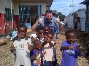 Dr. Brian Bird (Ph.D. '08, DVM '09) outside an Ebola Treatment Unit in Sierra Leone, with a group of kids who had recovered from the virus and were celebrating their discharge.