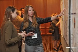 Hannah Laurence (on right) explains her research at the American Society of Clinical Investigators (ASCI) Joint Meeting in Chicago, Illinois. Photo credit: Randy Belice for the Howard Hughes Medical Institute